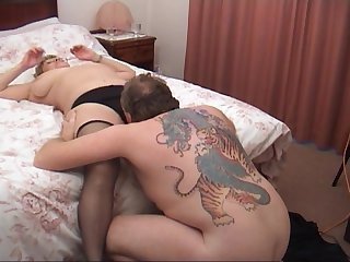 Elderly woman in stockings in ready for a tattooed man's prick